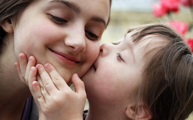 Kind küsst seine Mutter auf die Wange.