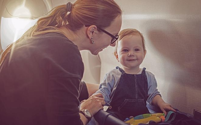 Mit dem Kind zu spielen beruhigt und beschäftigt das Baby während des Fluges