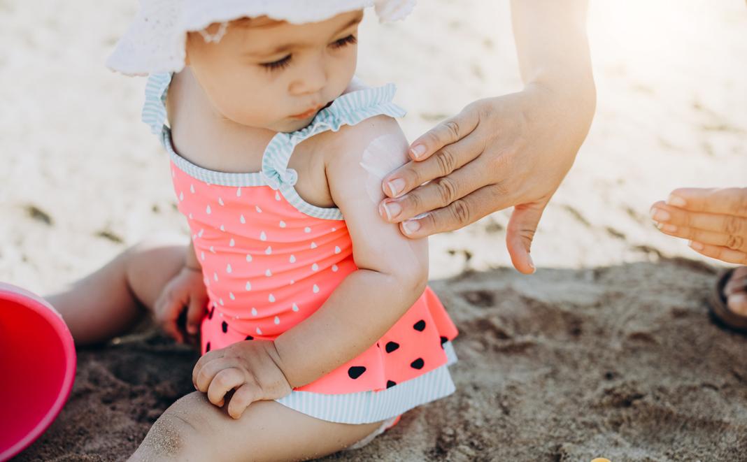 Sonnencreme auftragen bei Baby am Strand