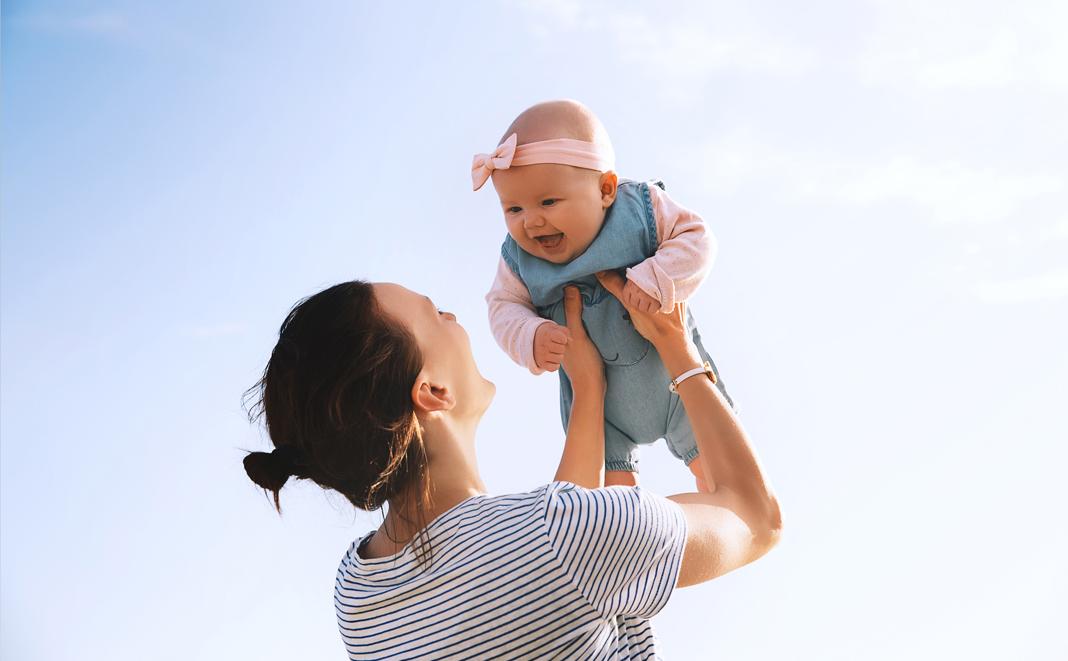 Alleinerziehende Frau hebt Baby hoch.