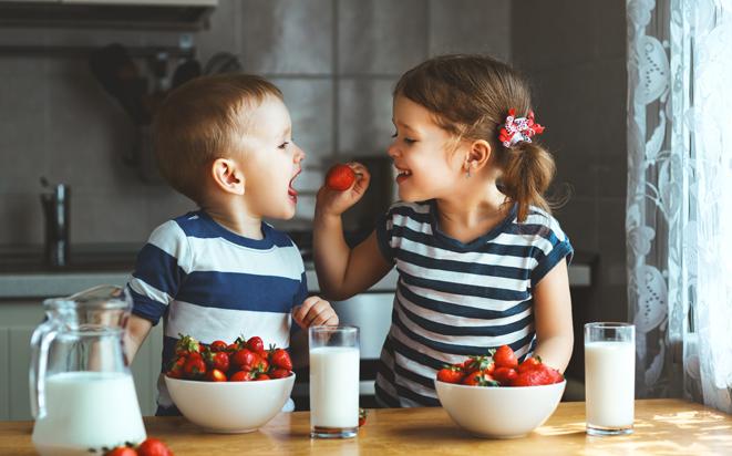 Zwillinge am Erdbeeren essen.